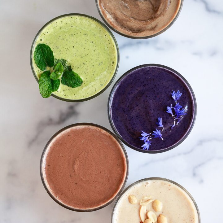 5 different protein shakes on a marble countertop.