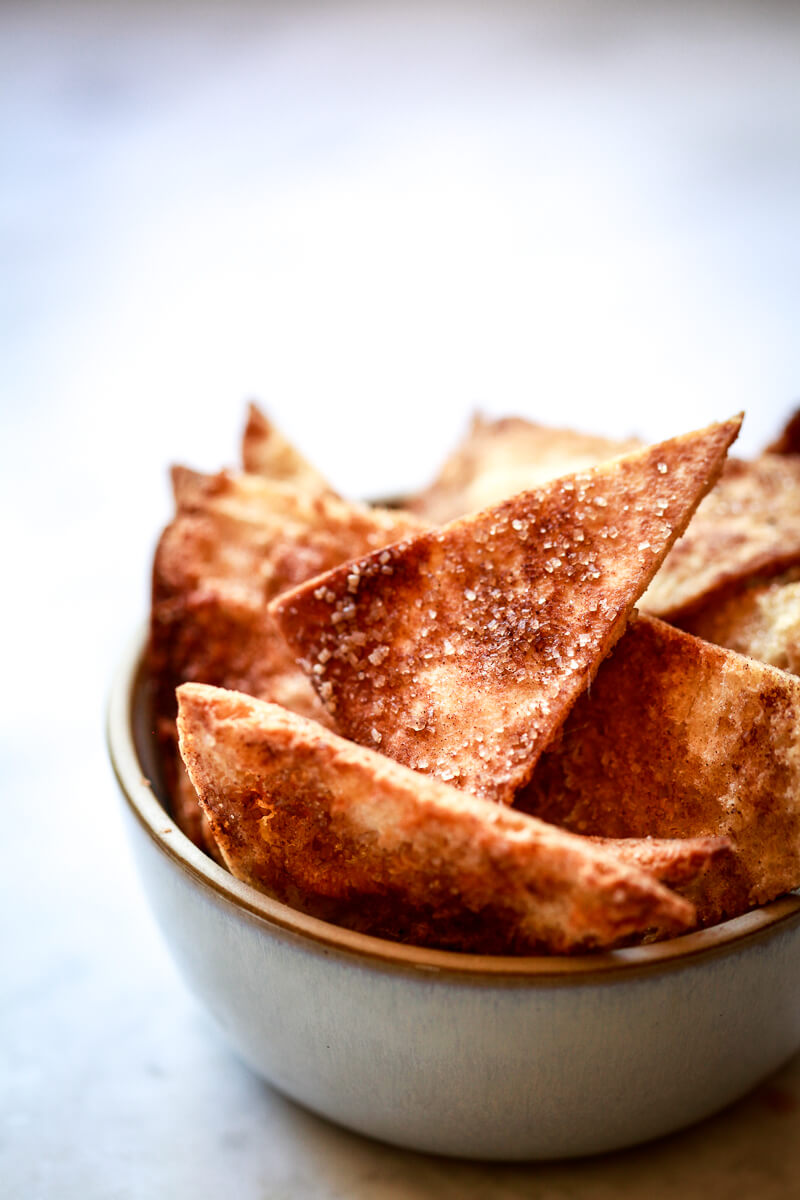 A ceramic bowl filled with homemade cinnamon sugar pita chips.