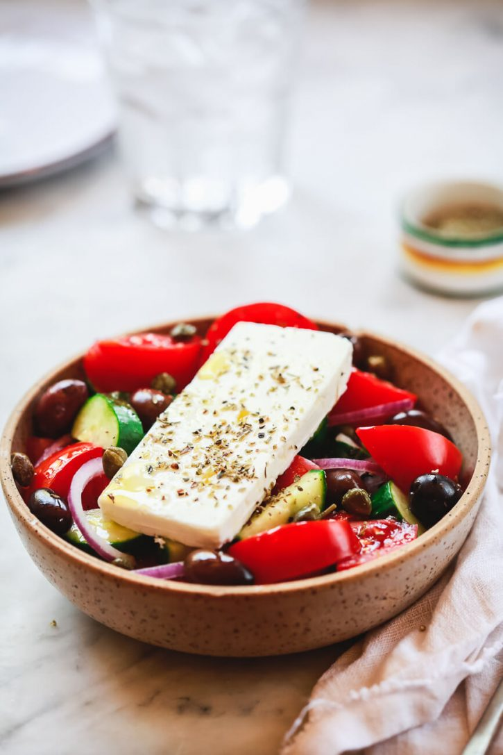 A photograph of a bowl filled with traditional Greek village salad made with tomatoes, cucumber, olives, onion, and topped with feta cheese.