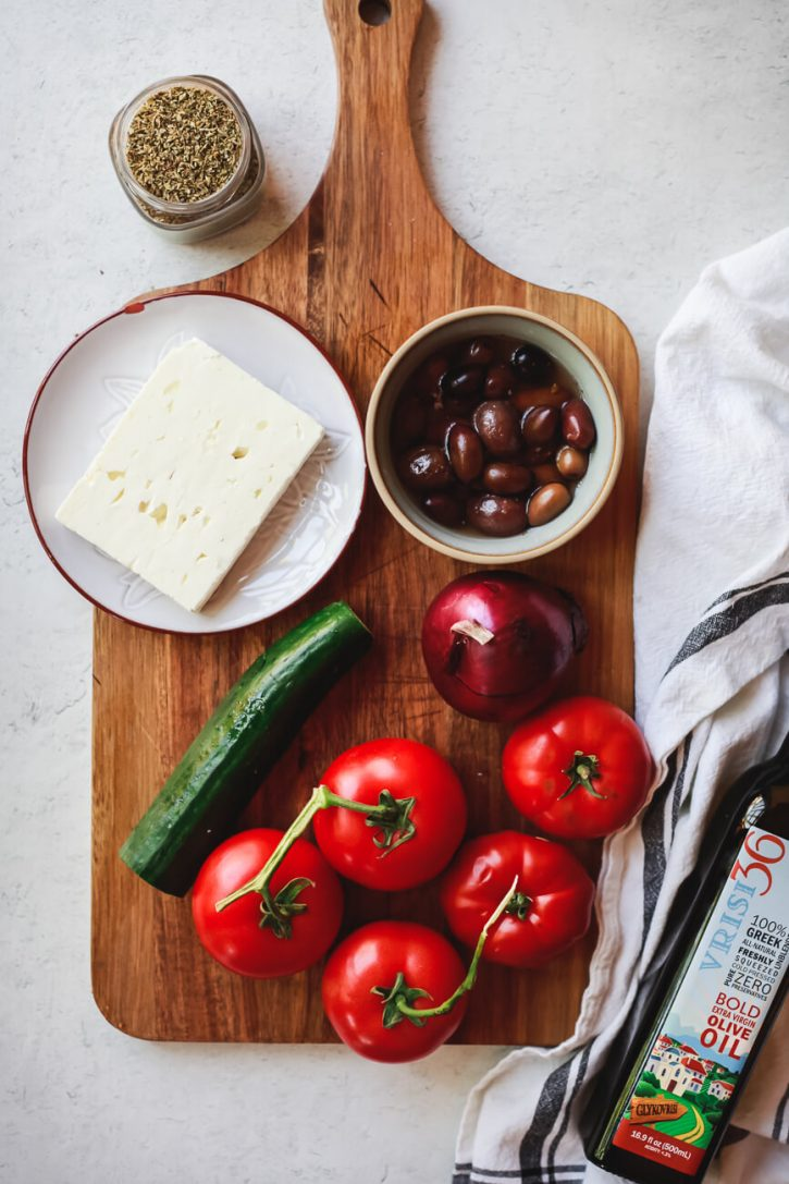 The ingredients for traditional Greek salad on a cutting board: tomatoes, cucumber, red onion, kalamata olives, feta, and oregano.