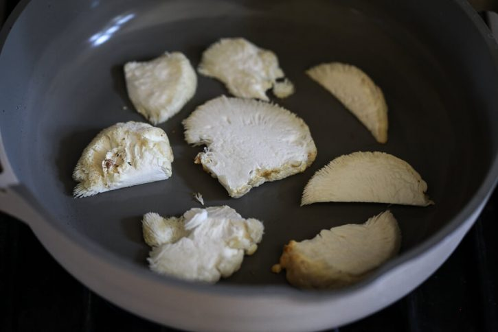Slices of lion's mane mushroom begin to cook in a dry skillet.