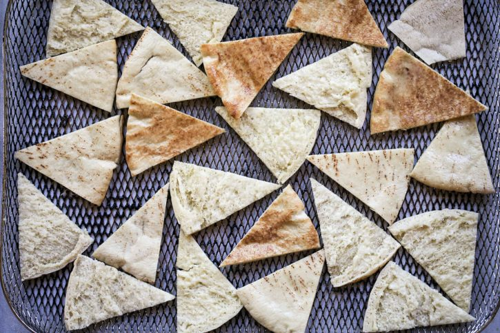 Pita chips in an air fryer basket.