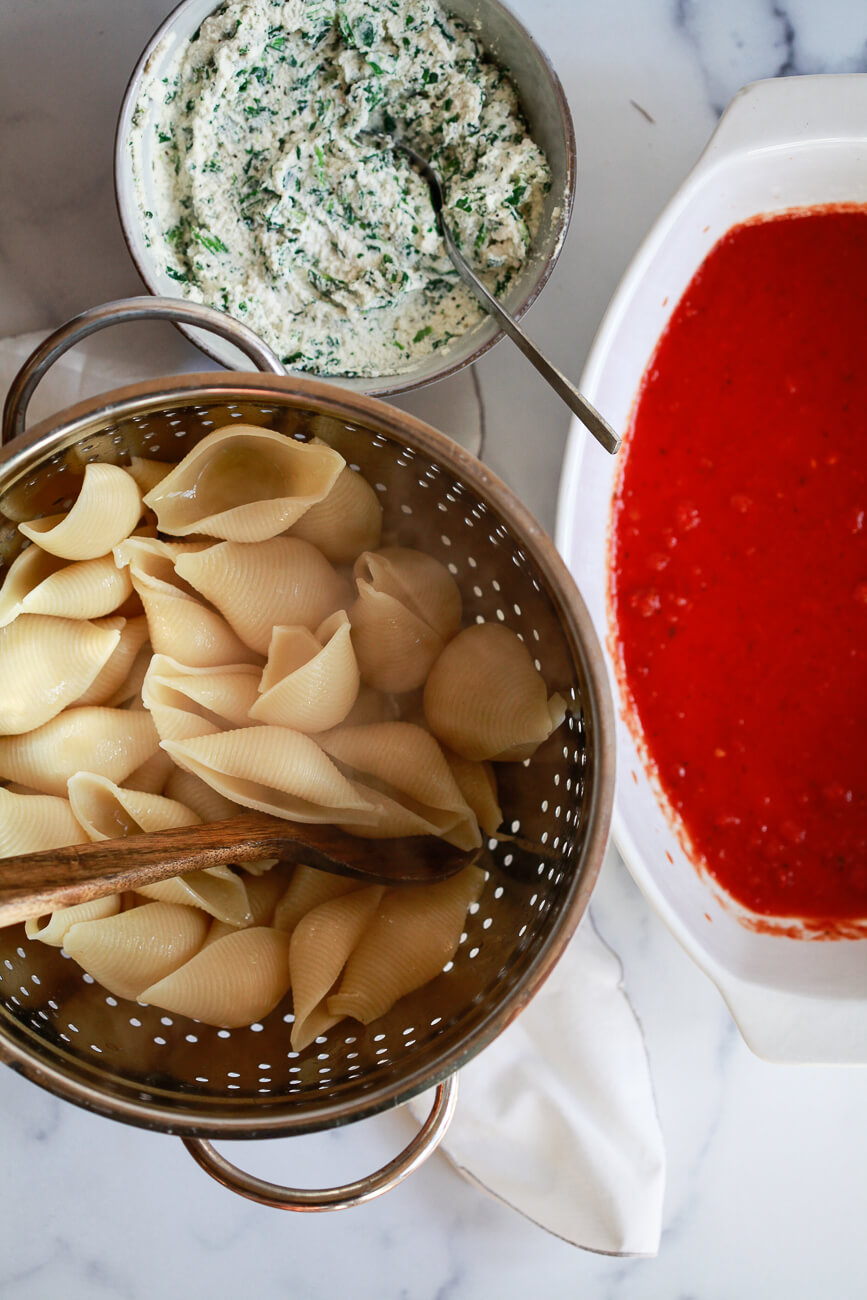 An overhead photo of cooked shell pasta in a colander, a bowl of ricotta filling, and a casserole dish filled with marinara sauce.