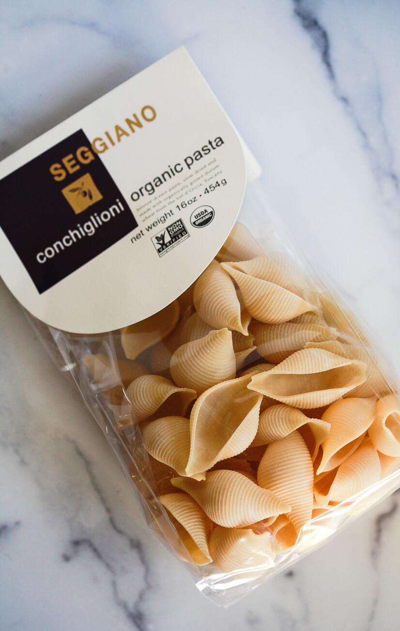 A bag of Seggiano conchiglioni organic pasta jumbo shells sits on a white marble countertop.