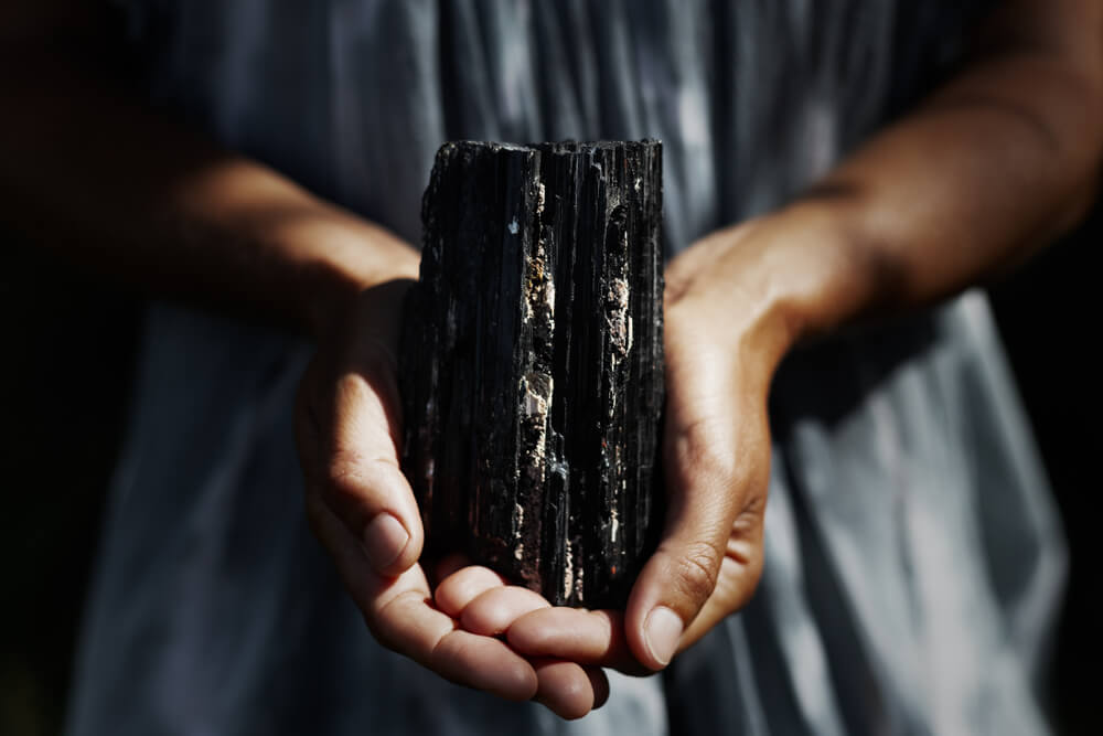 A beautiful image of hands holding a black tourmaline crystal.