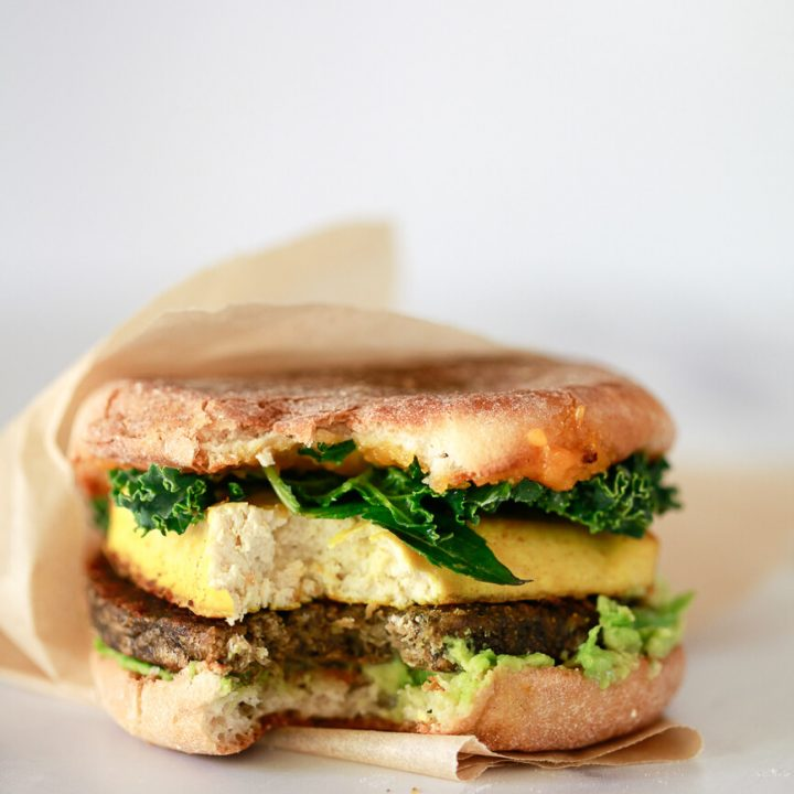 A close-up photo of a vegan breakfast sandwich with a bit out of it.