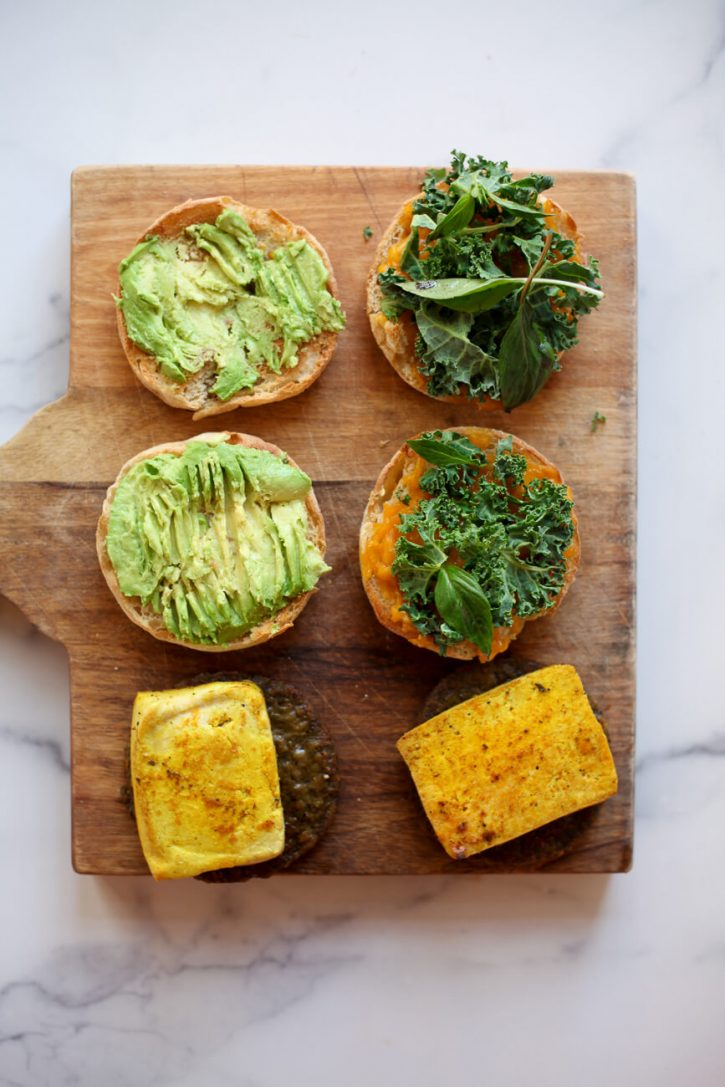 Vegan breakfast sandwiches are assembled on a cutting board.