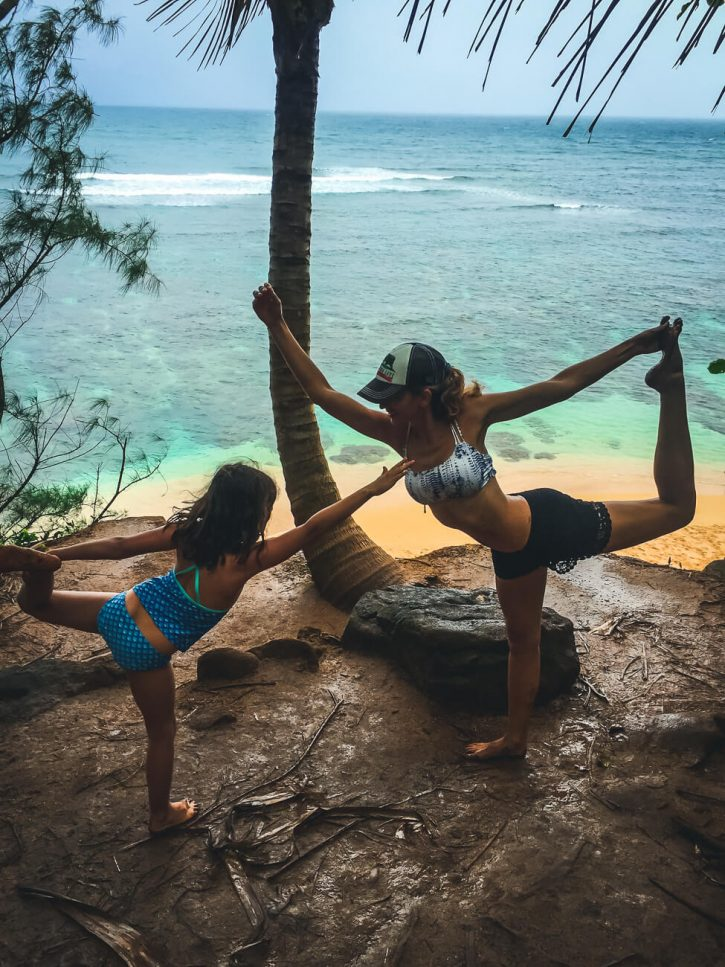 A mother and daughter in dancer's pose barefoot in Hawaii.
