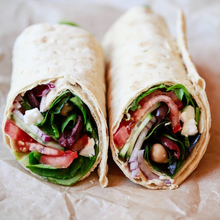 Mediterranean wraps cut in half filled with greens, tomato, feta, olives, cucumber, and onions.
