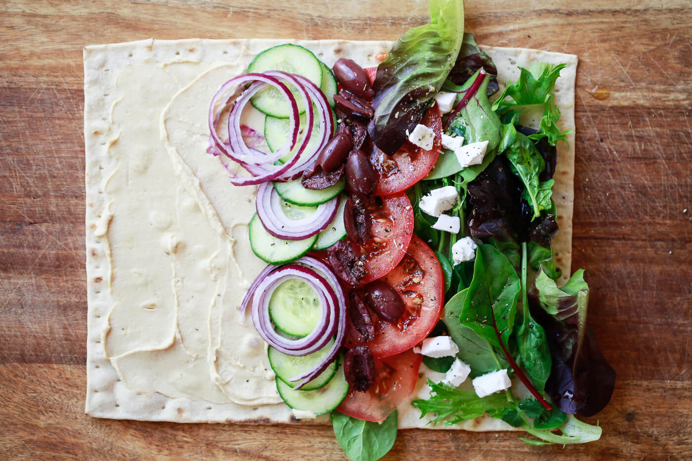 A piece of lavash flatbread is covered in hummus and vegetables.