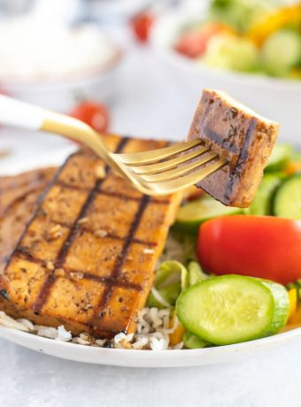 A bowl of veggies and rice topped with grilled tofu.