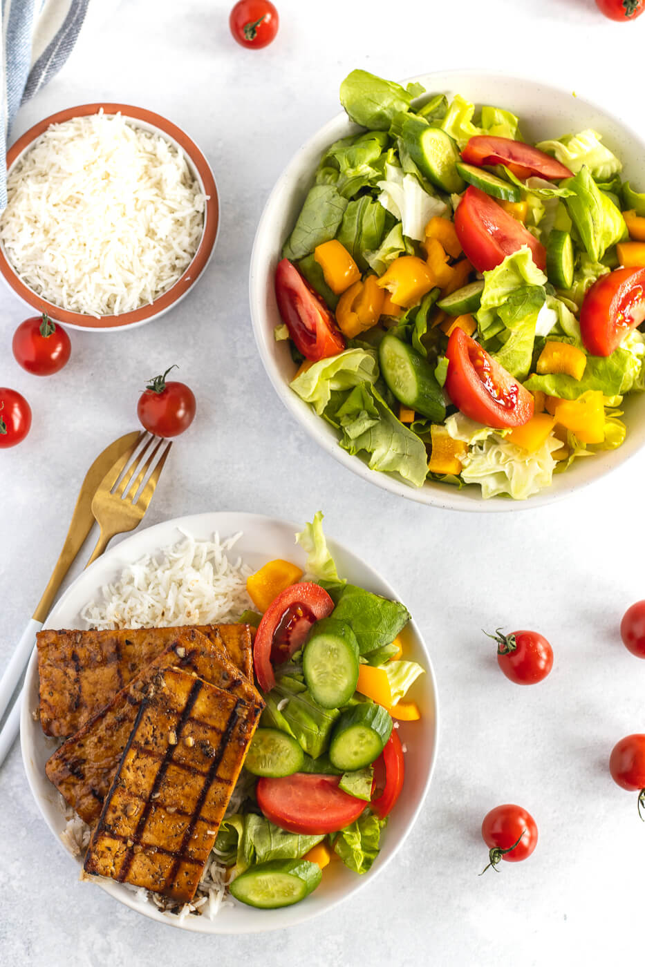 An overhead photo of grilled tofu on top of rice and vegetables. A salad is on the side. This is a great vegetarian BBQ recipe.