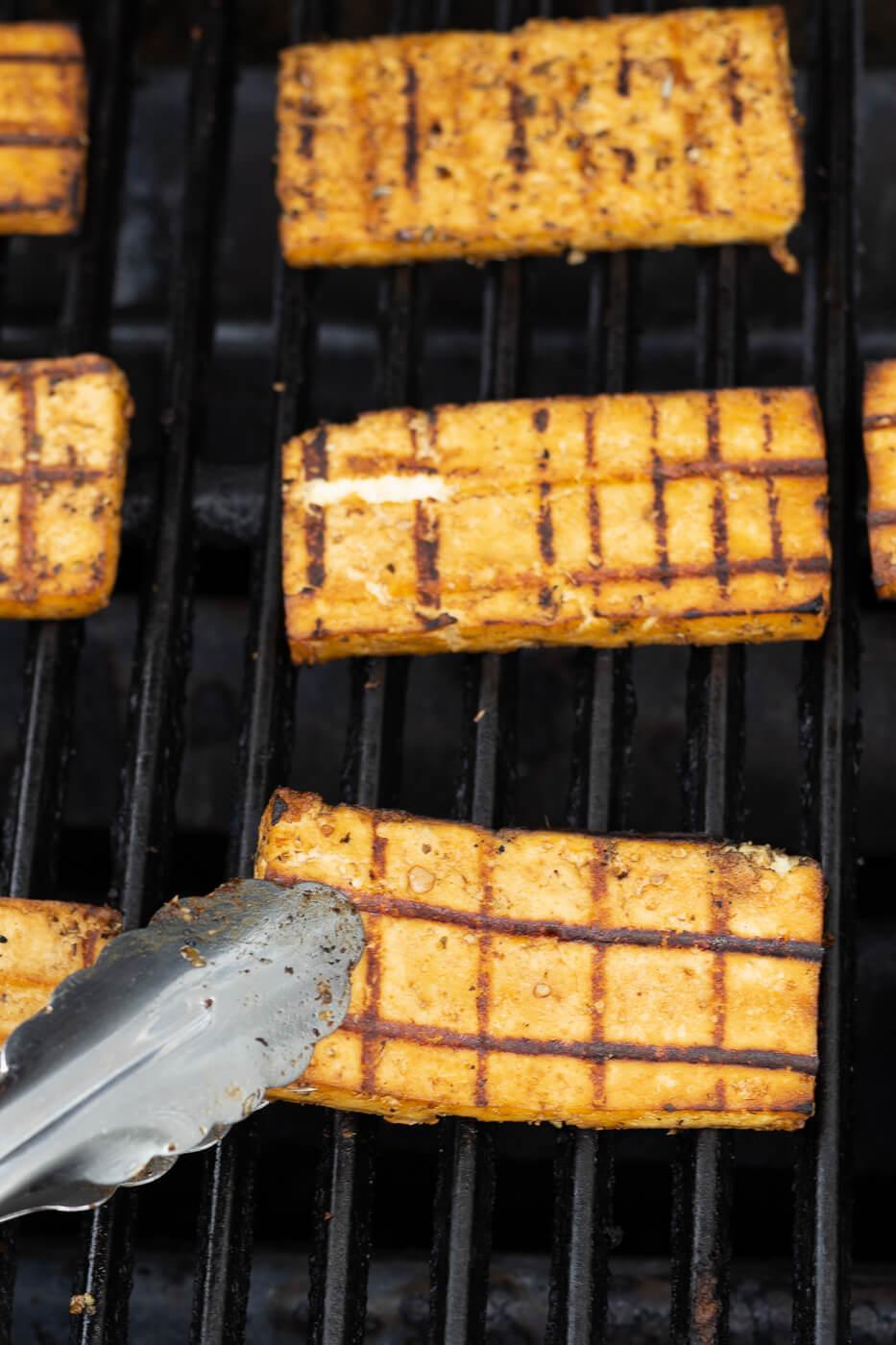 Tongs turn tofu steaks on a grill.