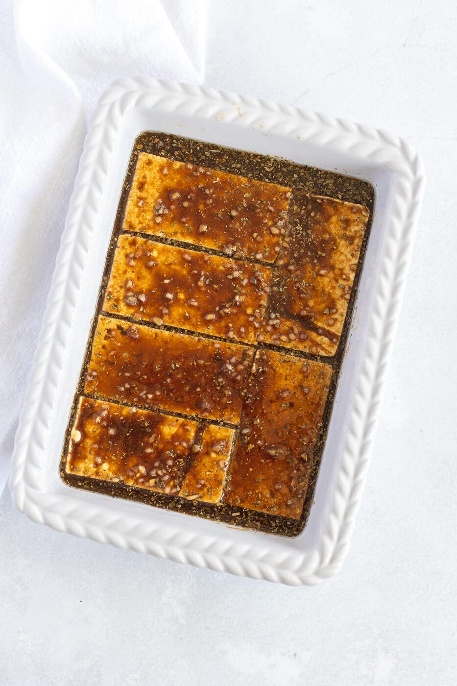 Sliced tofu marinates in a white dish.