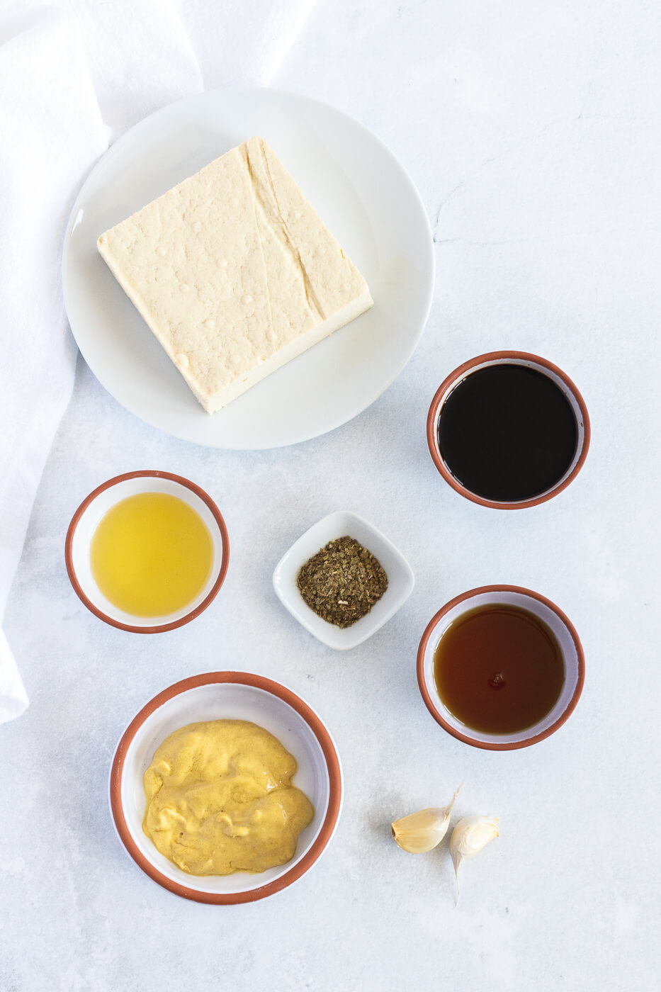 The ingredients for marinated tofu are pictured in small bowls on a white countertop next to a block of tofu.