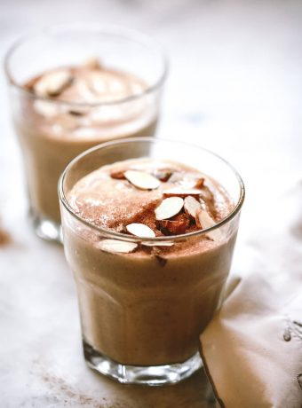 close up photo of a healthy date shake topped with slivered almonds and medjool dates