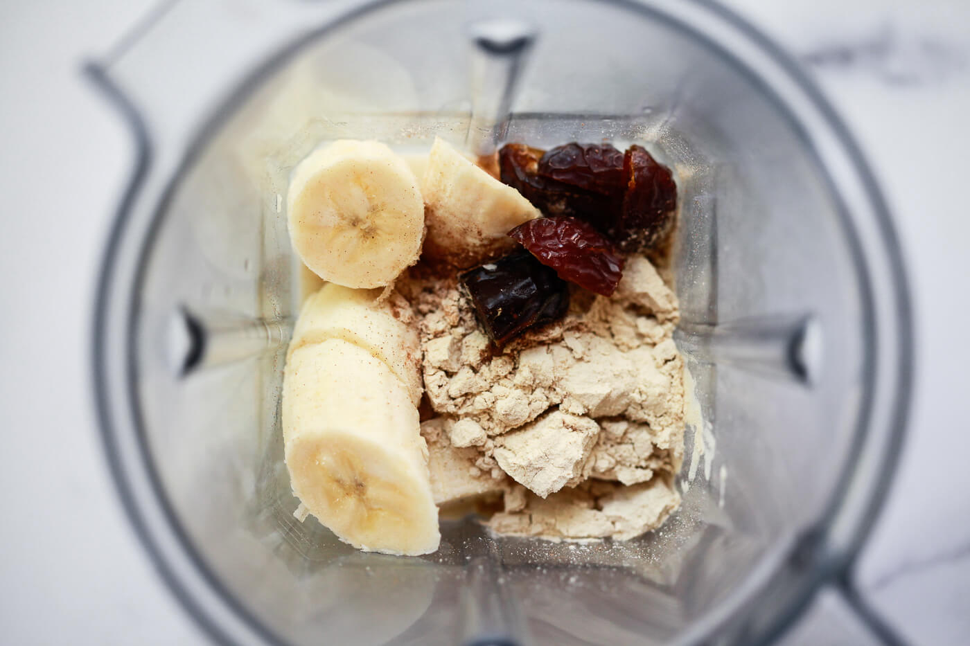 All the ingredients for a healthy date shake shown in a Vitamix blender.