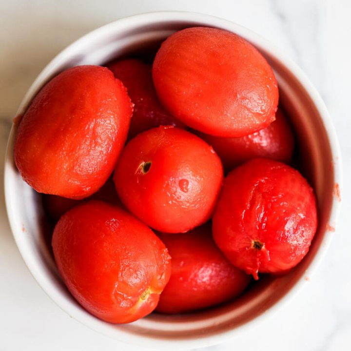 A bowl of peeled Roma tomatoes.