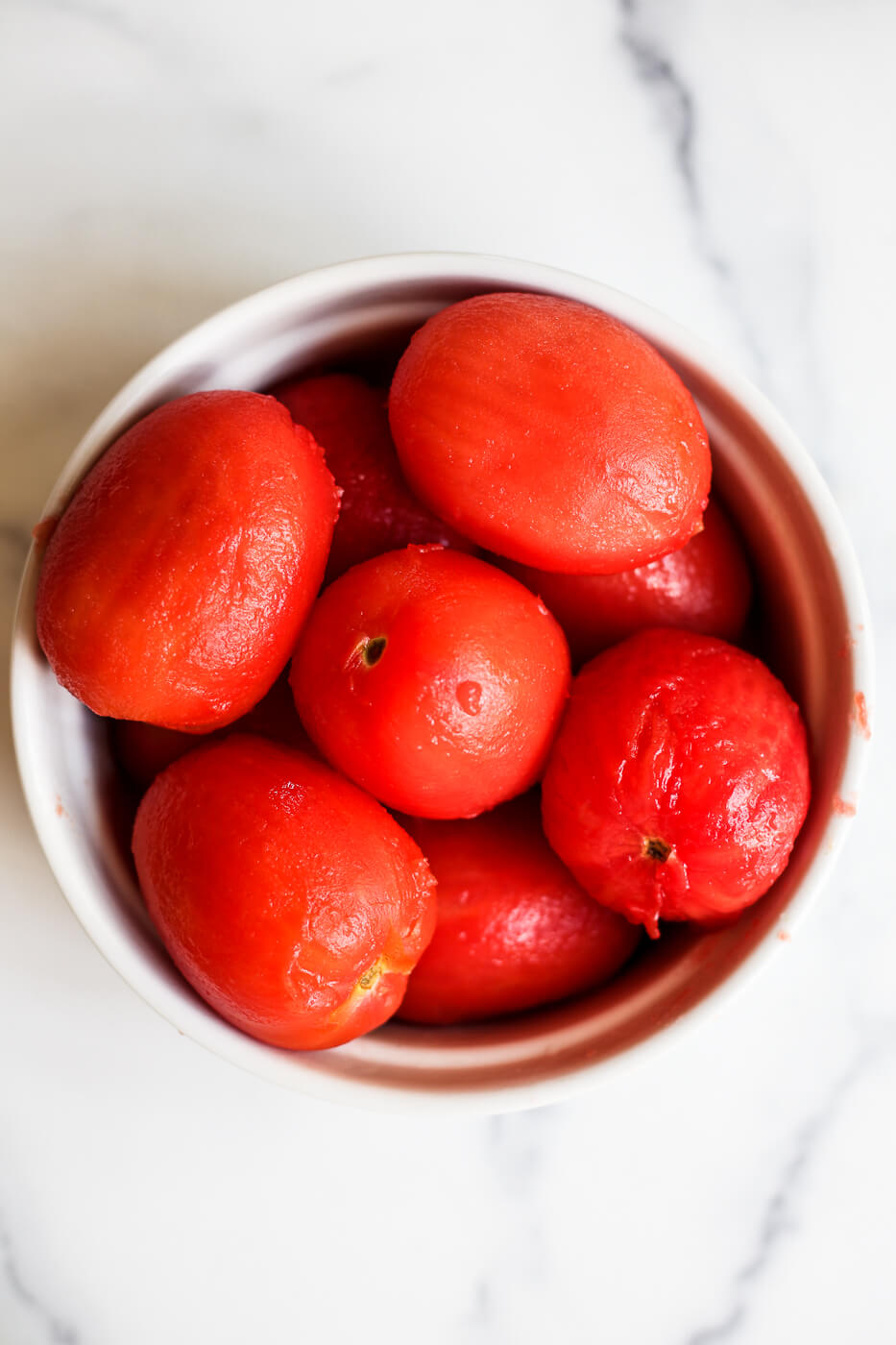 An overhead photo of a bowl of blanched peeled tomatoes on a marble countertop.
