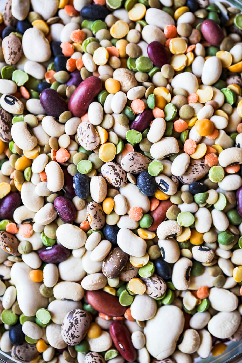A close-up photo of mixed legumes including beans and split peas.