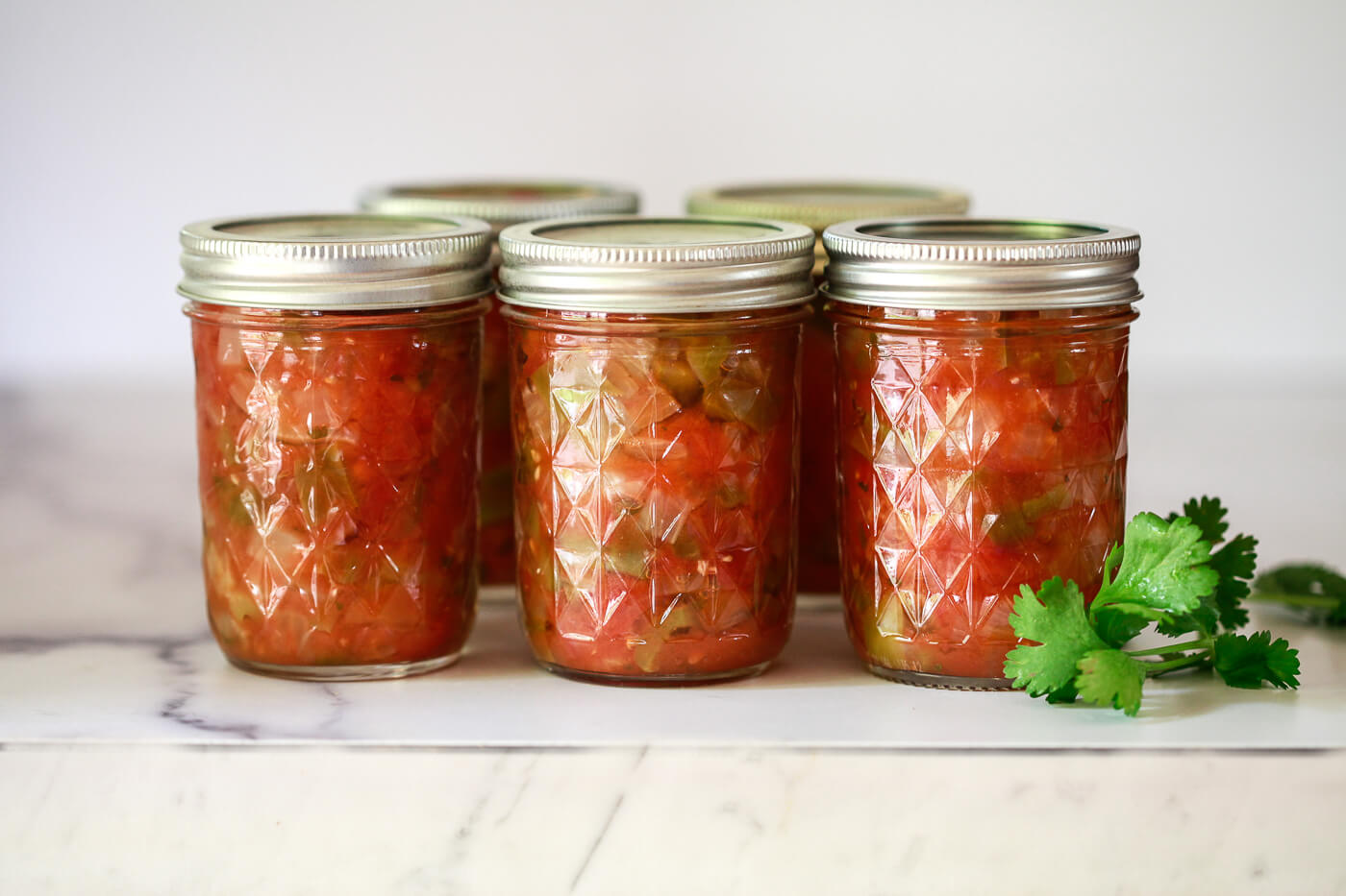 8 oz. Ball jars filled with homemade canned salsa on a marble counter.
