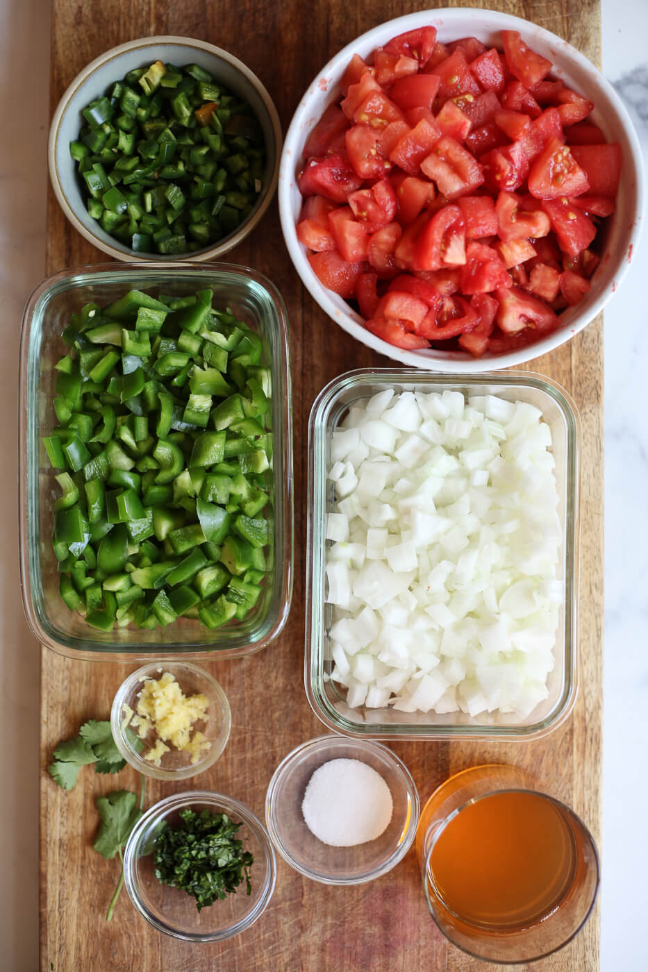 The ingredients for homemade canned salsa are prepared on a cutting board and include tomatoes, bell pepper, onion, jalapeno, garlic, cilantro, salt, and apple cider vinegar.