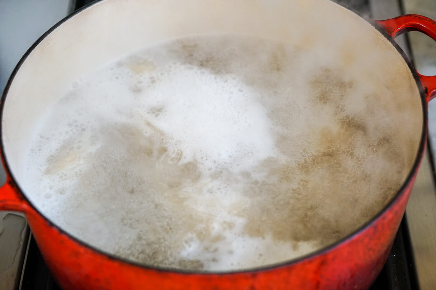 Soaked sea moss boils in a large pot on the stove.