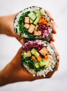 A close-up photo of hands holding a sushi burrito (sushirrito)