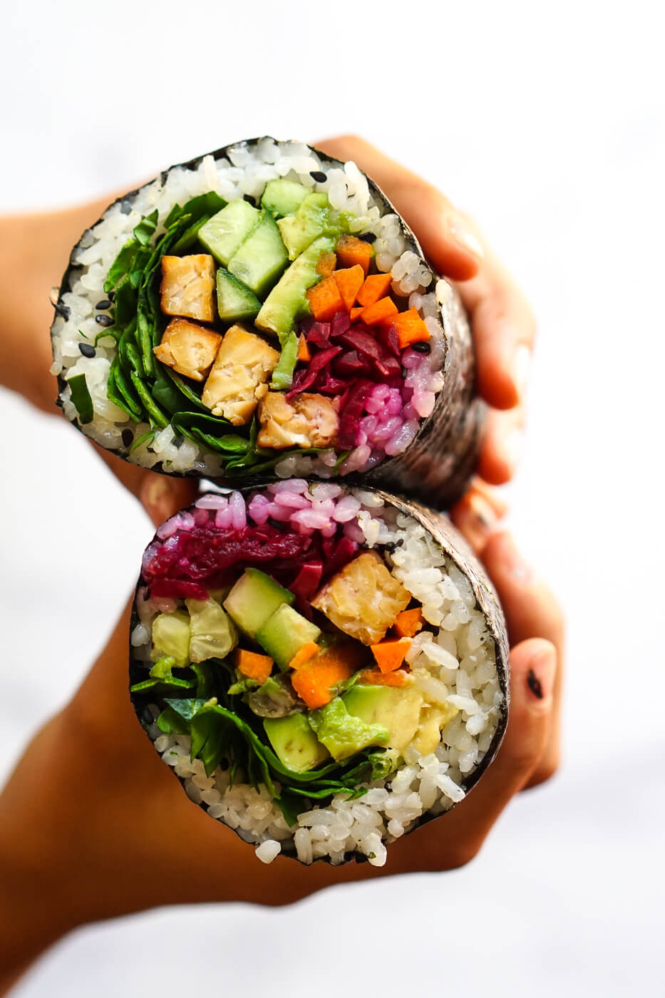 Photograph of hands holding two halves of a sushi burrito filled with vegetables and tempeh.