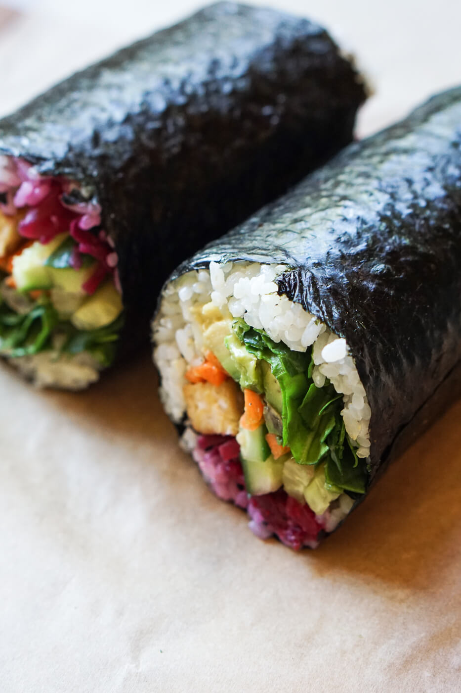 A close up photo of a vegan sushi burrito filled with spinach, avocado, cucumber, carrots and tempeh.