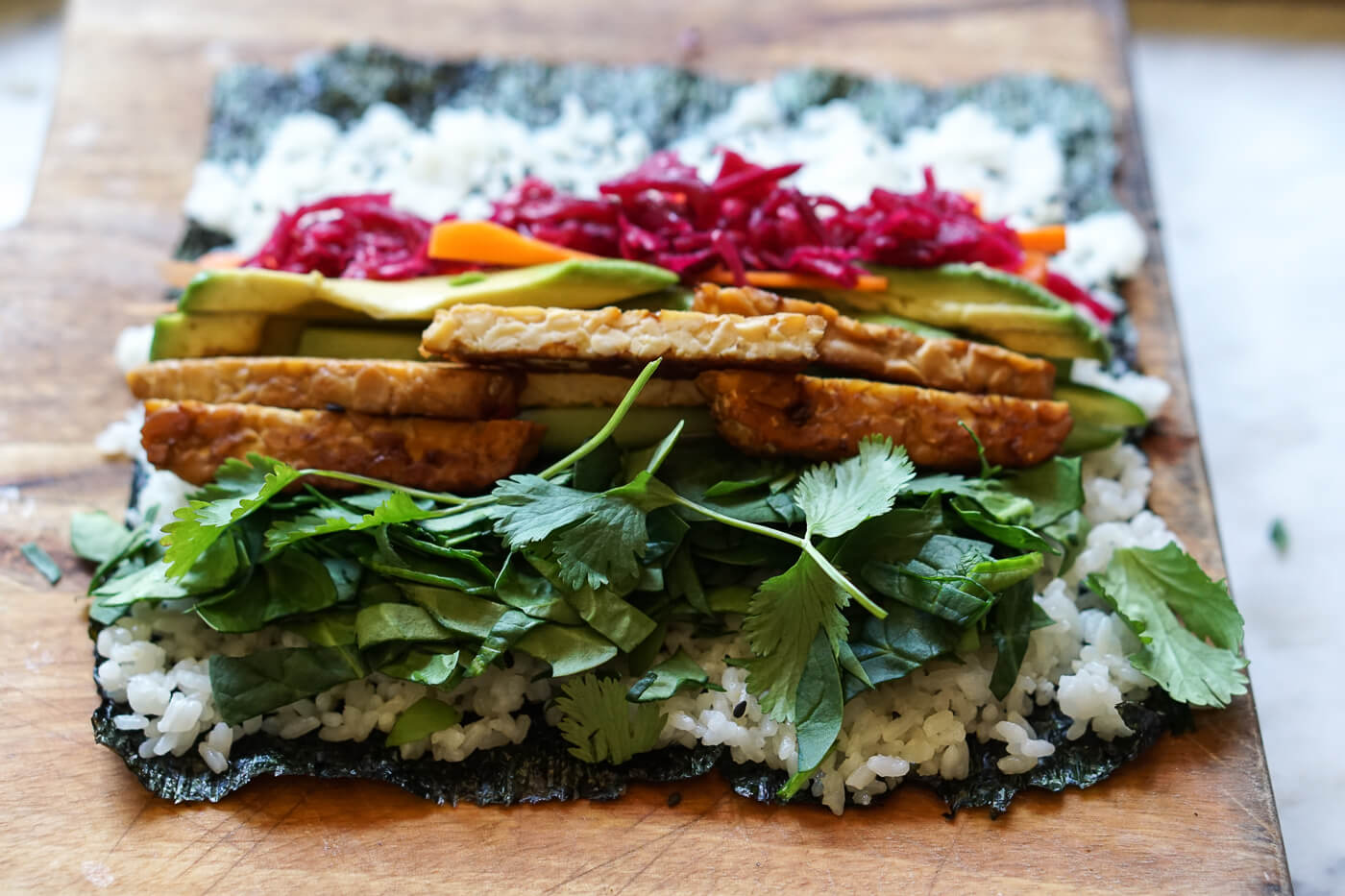 Sushi burrito fillings are placed on top of nori and rice.