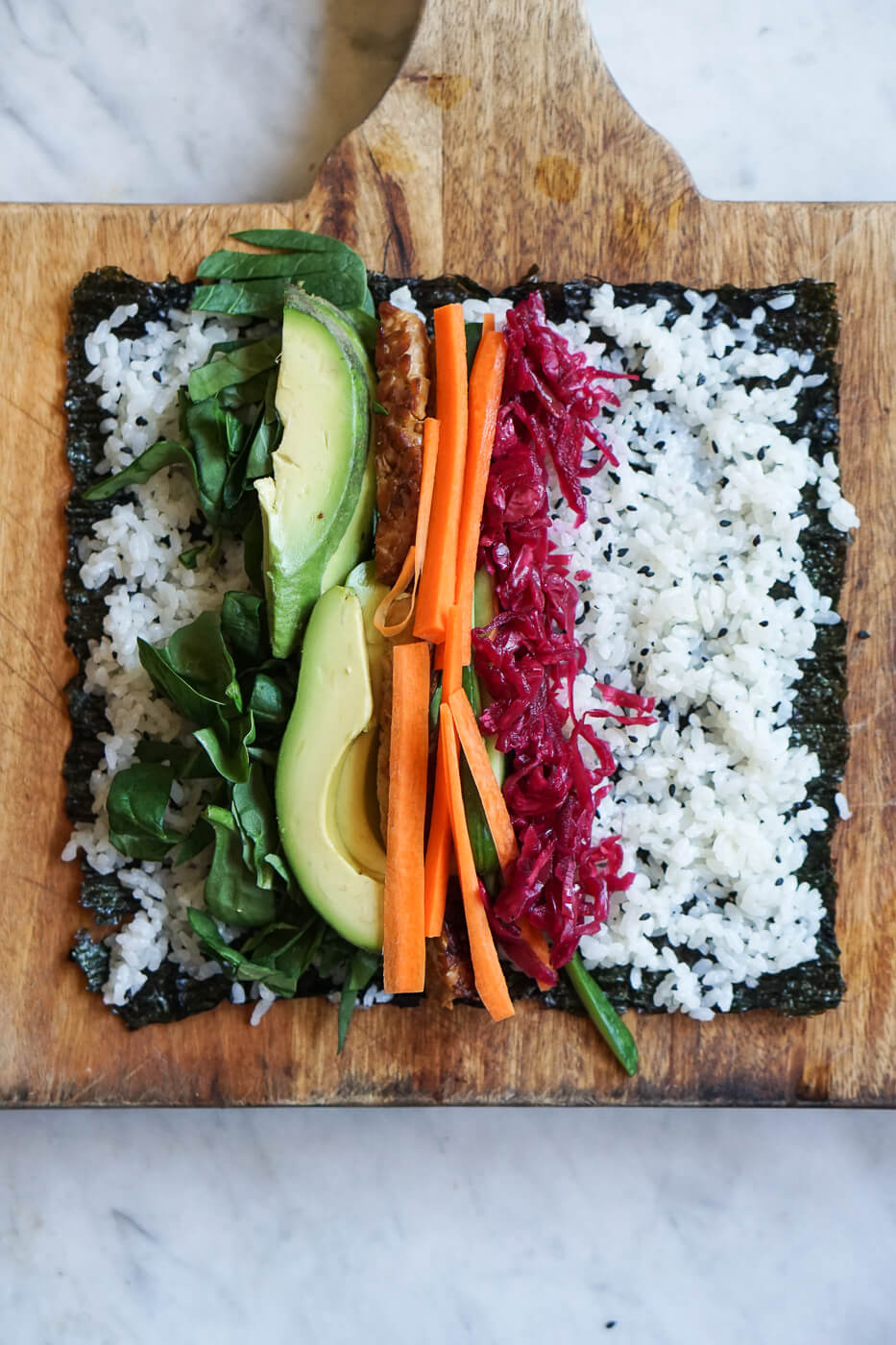 A piece of nori is topped with sushi rice and vegetables.