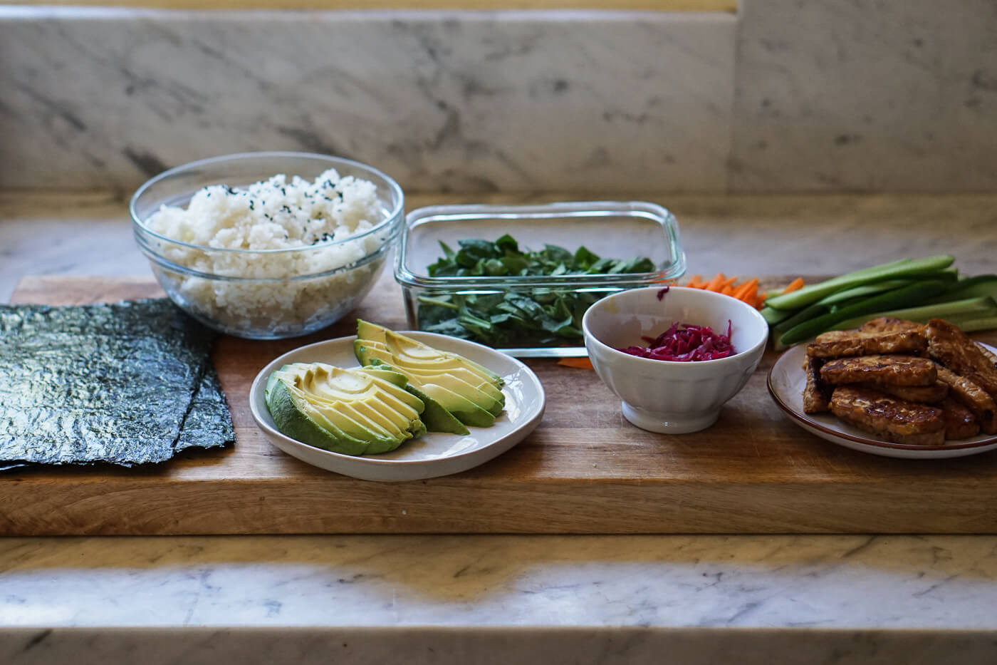 The ingredients for sushi burritos set on a cutting board.