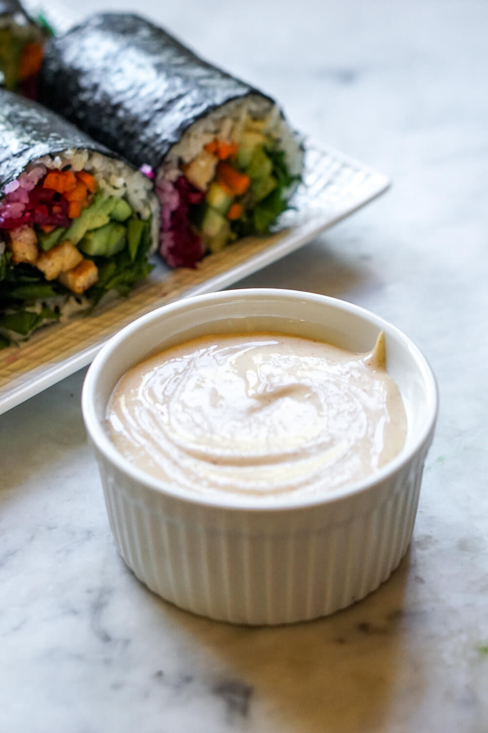 A photo of a white ramekin filled with homemade Japanese yum yum sauce. Sushi rolls can be seen in the background.