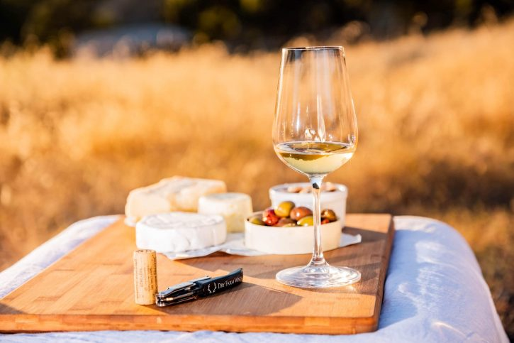 A beautiful outdoor picnic with white wine, cheese, and olives.