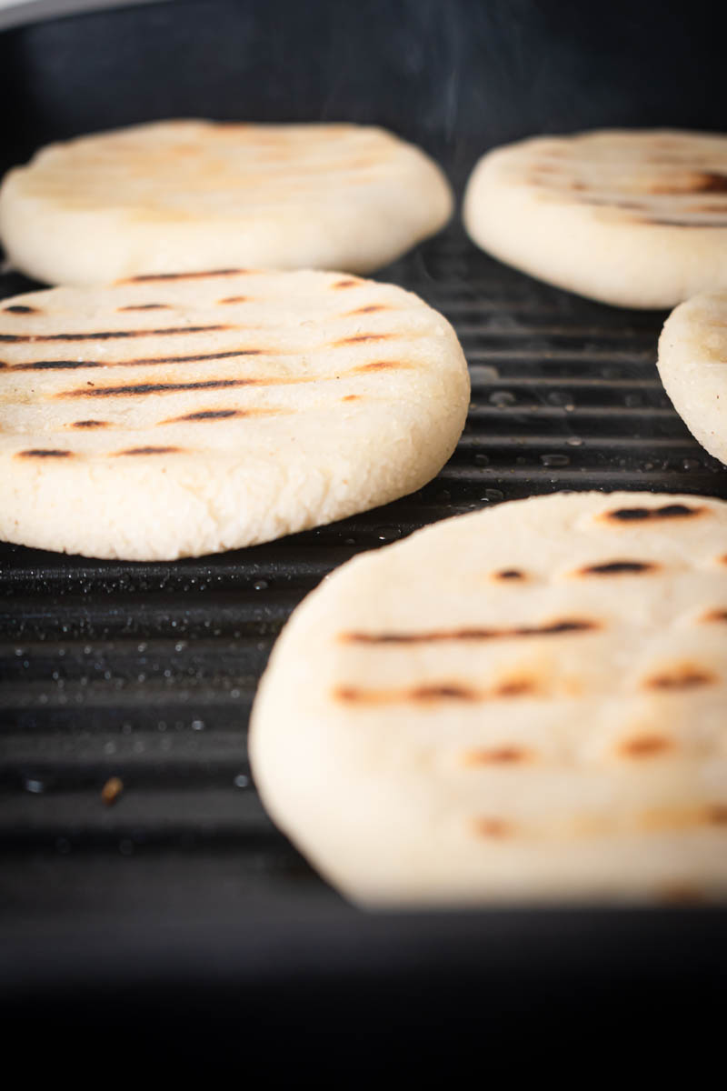 Arepas Venezolanas are grilled on a grill pan.