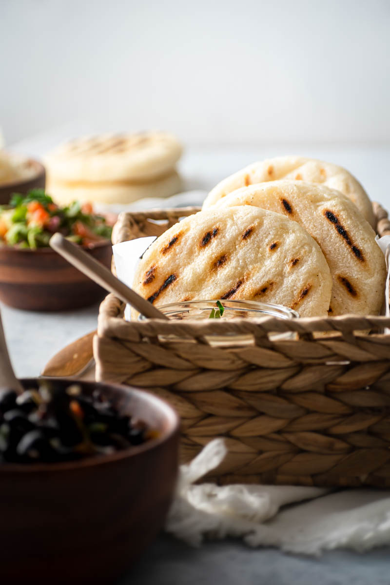 Arepas in a basket with black beans.