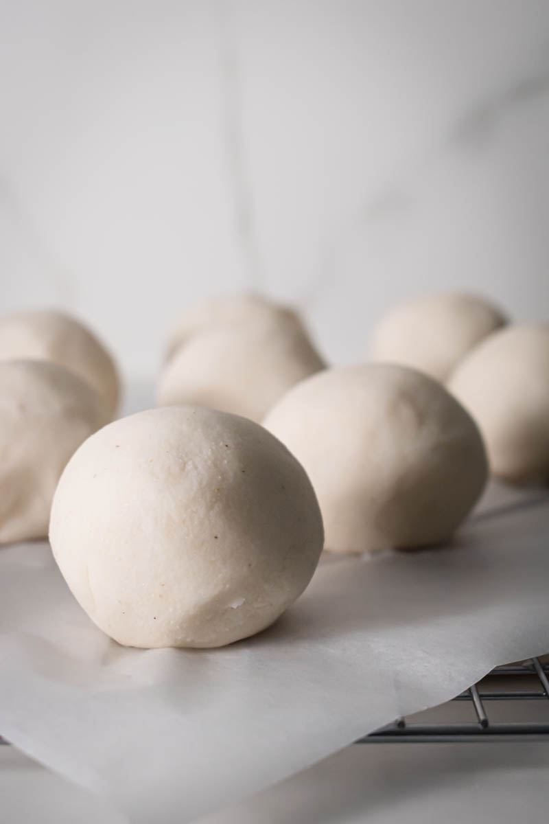8 balls of Arepa dough on a counter.