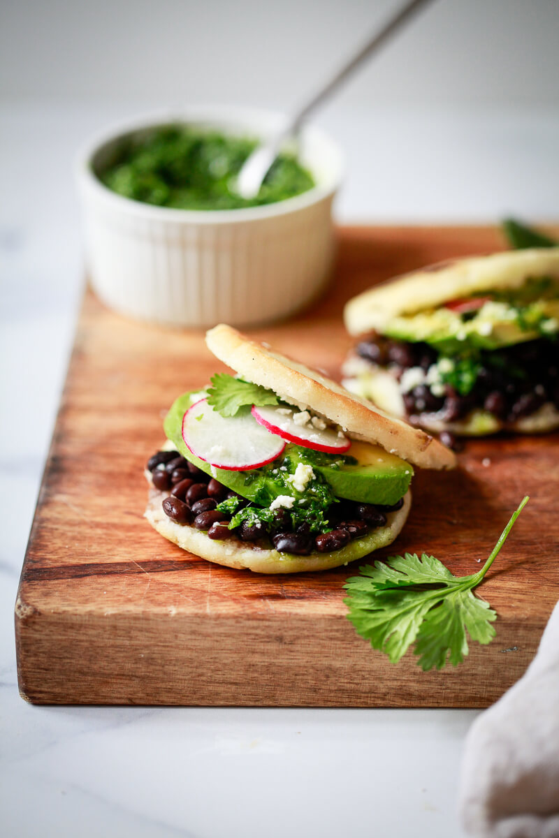 Two arepas filled with black beans, avocado, chimichurri sauce, queso fresco, and radish slices.