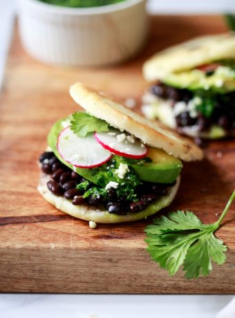 Close-up photo of an arepa filled with black beans, cheese, and avocado.