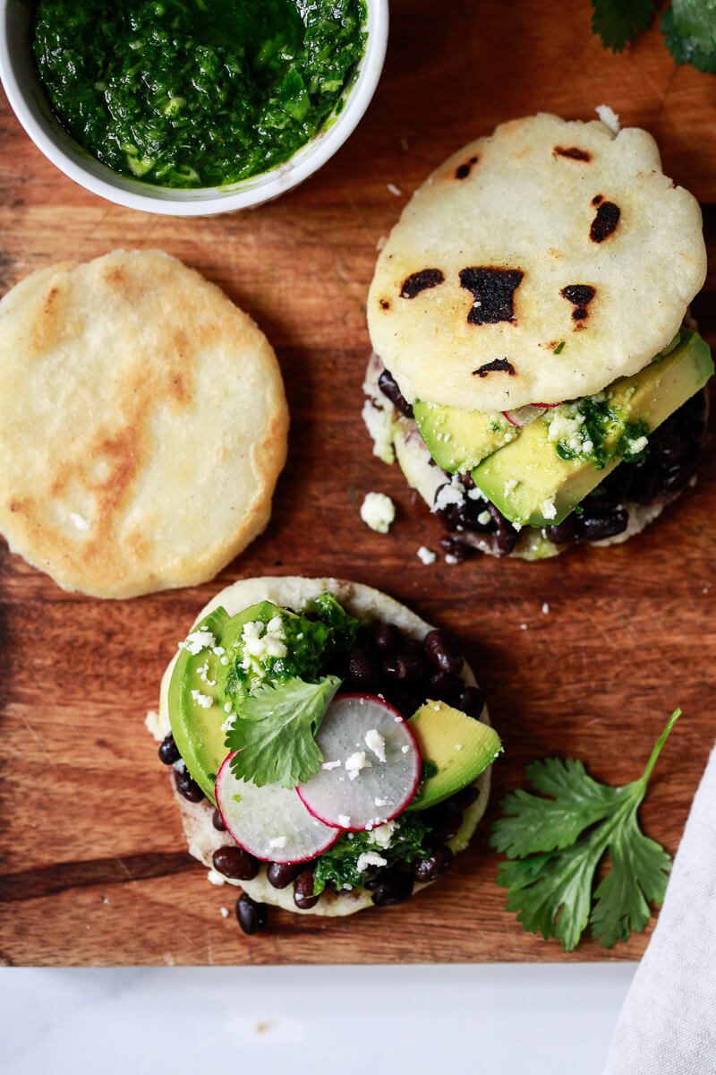 Homemade Arepas Venezolanas topped with black beans and avocado on a cutting board with a bowl of chimichurri sauce on the side.