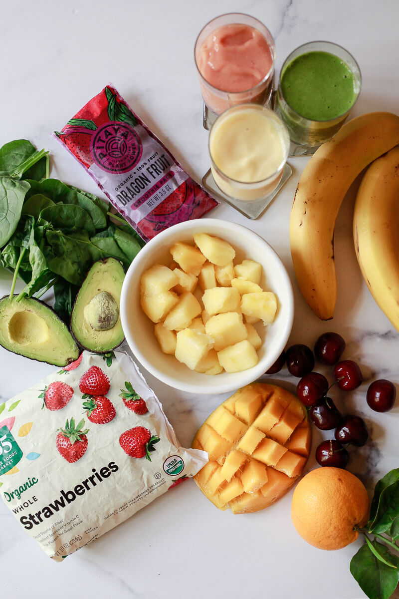 Ingredients for making healthy smoothie recipes on a marble countertop include frozen fruit, avocados, spinach, Dragon fruit packs, bananas, oranges, cherries and mango.