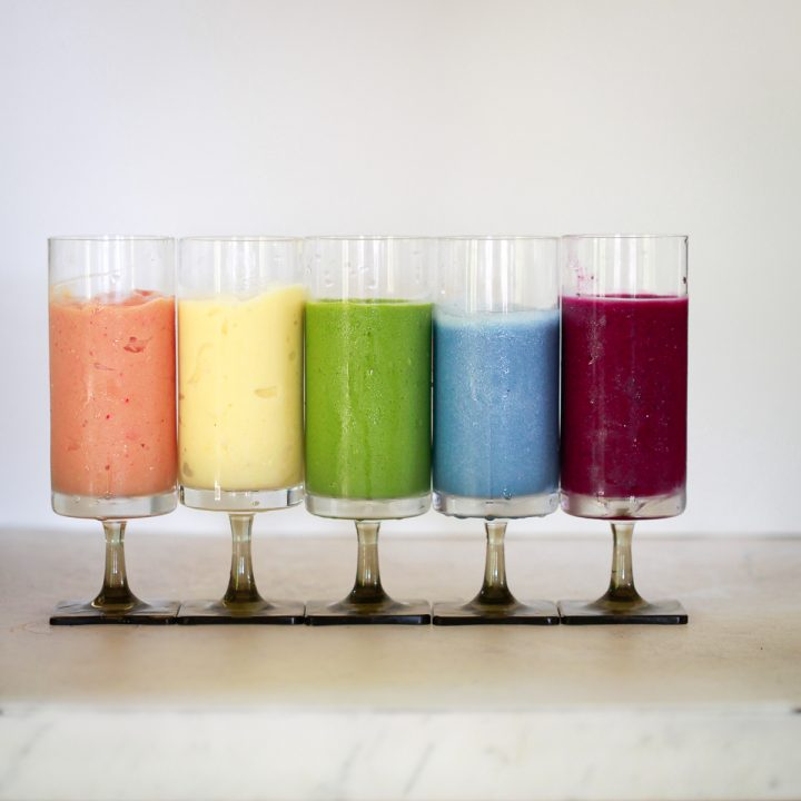 5 colorful healthy smoothies on a marble countertop.