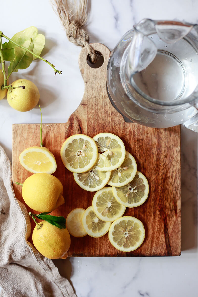 A cutting board topped with sliced lemons sits next to a pitcher of water.