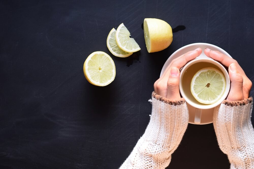 Hands hold a hot mug filled with hot lemon water.