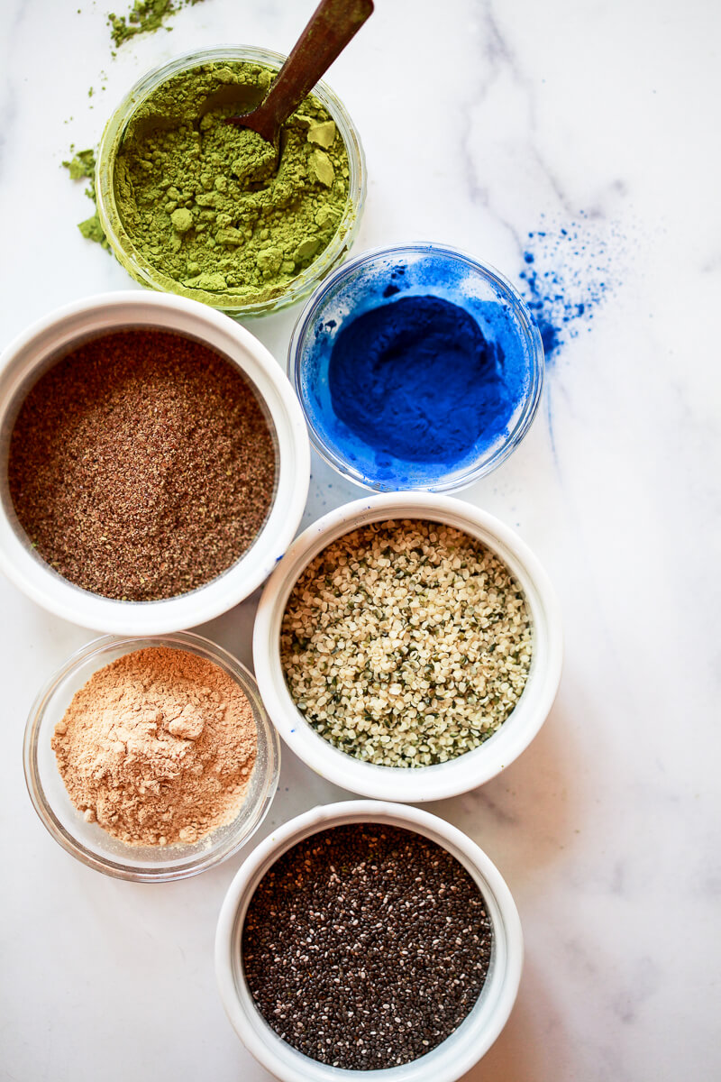 An overhead photo of superfood smoothie supplements. These include matcha powder, blue spirulina, flax, hemp, maca, and chia seeds.