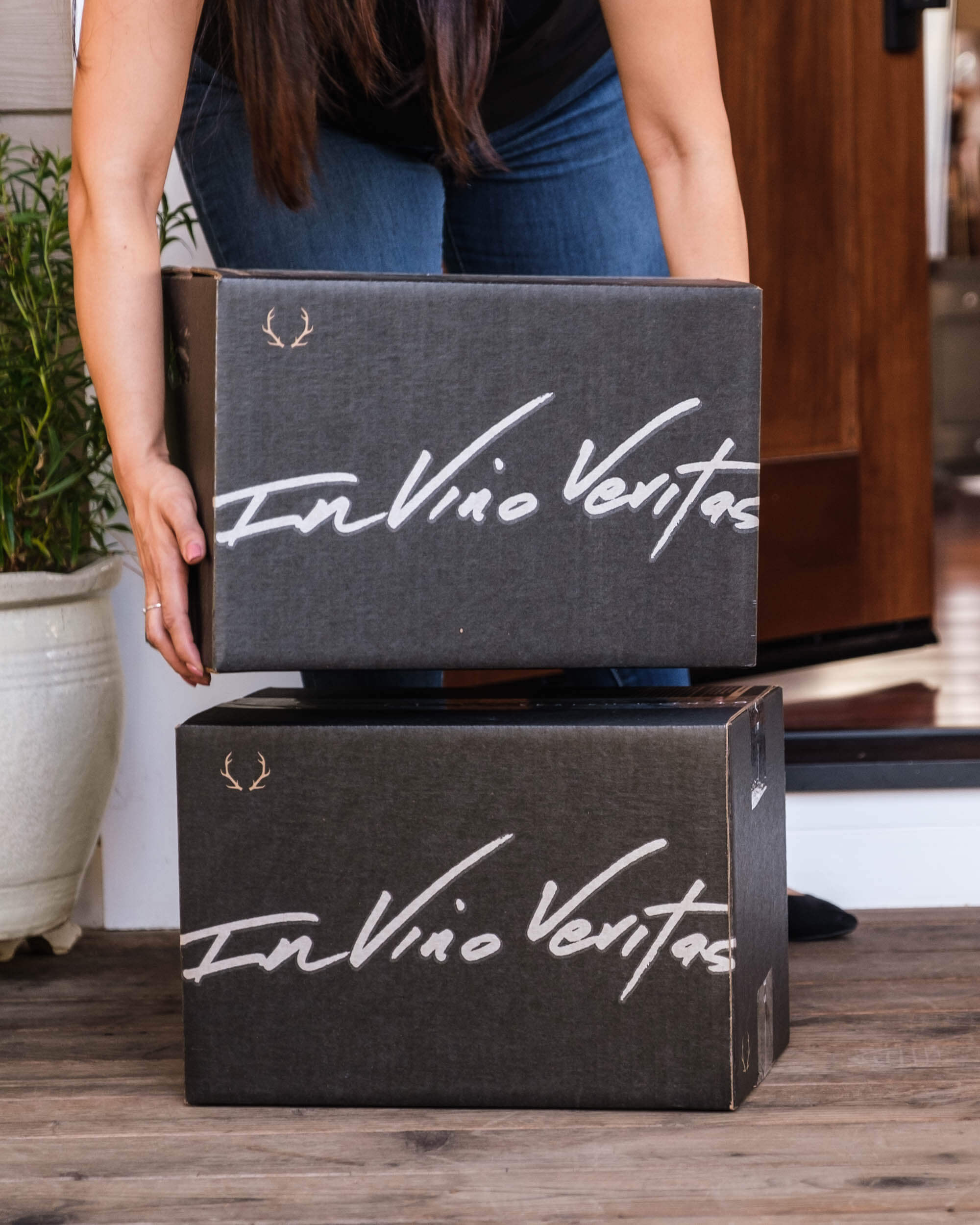 """A woman picks up a box from Dry Farm Wines off a porch. The boxes read """"In Vino Veritas"""""""
