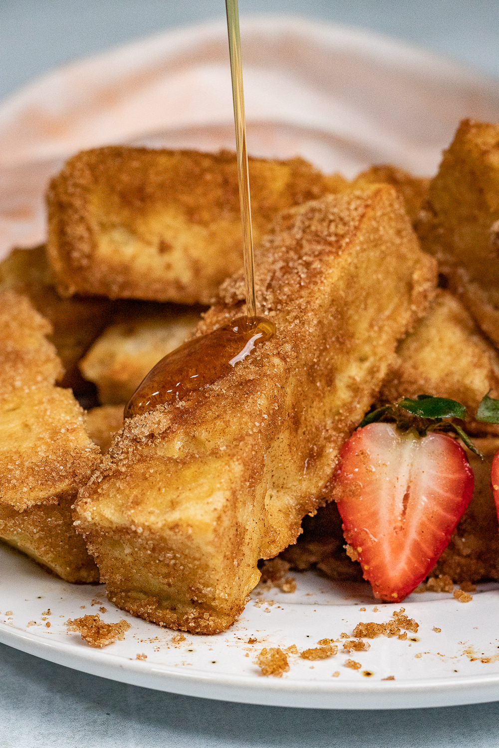 Maple syrup is poured over cinnamon sugar French toast sticks that were cooked on a griddle.