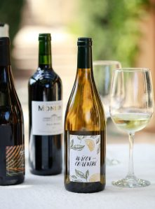 Three bottles of Dry Farms Wines natural sugar free wine on an outdoor table.