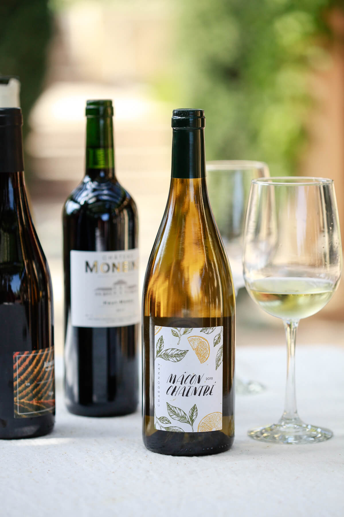 Three beautiful bottles of natural wine on an outdoor table. These are all natural wines from Dry Farm Wines.